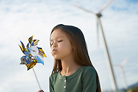Girl (5-6) blowing toy windmill at wind farm