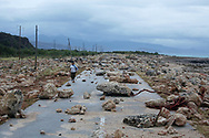 A woman walks in a highway blocked by rocks after the passage of hurricane Matthew on the coast of Guantanamo province, Cuba, October 5, 2016. REUTERS/Alexandre Meneghini