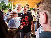 "20 AUGUST 2019 - PROLE, IOWA: Former Vice President JOE BIDEN poses for a selfie with a man wearing a ""Moscow Mitch"" tee shirt after his campaign appearance in Prole. Vice President Biden is campaigning in Iowa to be the Democratic nominee for the US Presidency. He spoke to about 200 people in Prole Tuesday afternoon. Iowa traditionally hosts the first event of the presidential election cycle. The Iowa caucuses are Feb. 3, 2020.          PHOTO BY JACK KURTZ"