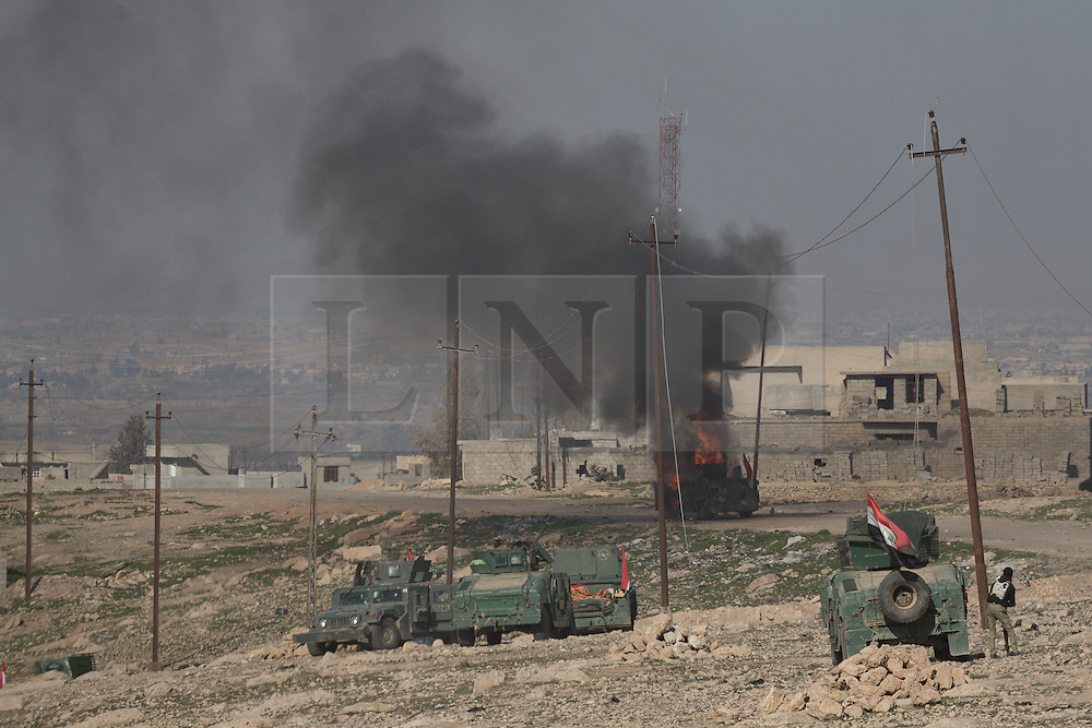 Licensed to London News Pictures. 20/02/2017. Albu Saif, Iraq. As an Iraqi Security Forces Humvee burns, other vehicles of the Iraqi Emergency Response Division advance towards Albu Saif as they take part in the offensive to retake western Mosul from the Islamic State.<br /> <br /> The settlement of Albu Saif is located on high ground overlooking Mosul Airport and as such is a strategic point that needs to be taken as part of the operation to retake the western side of Mosul. Photo credit: Matt Cetti-Roberts/LNP