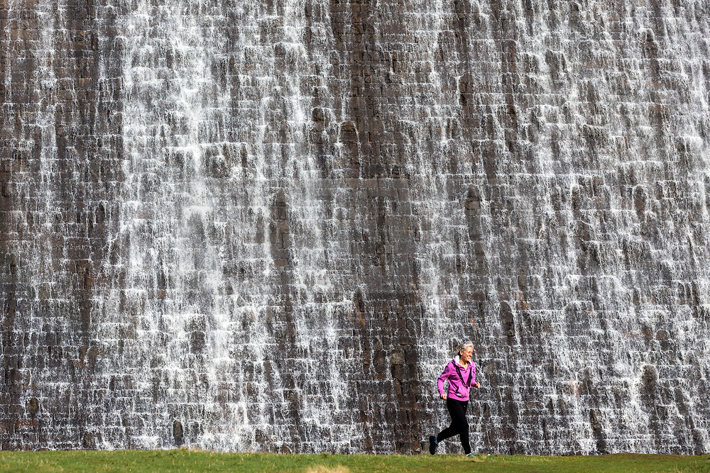 © Licensed to London News Pictures. 20/03/2019. Derwent UK. A lady walks her dog past the water overflowing Derwent dam in the Upper Derwent Valley, Derbyshire this morning. Photo credit: Andrew McCaren/LNP