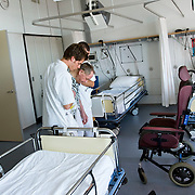 Nederland Rotterdam  31-08-2009 20090831 Foto: David Rozing .Serie over zorgsector, Ikazia Ziekenhuis Rotterdam. Afdeling neurologie, stroke unit, revalidatie oefeningen bejaarde man op zaal. Broeders ondersteunen een patient tijdens oefeningen om opnieuw te leren lopen en brengen hem terug naar zijn rolstoel. De patient heeft een beroerte gehad en daardoor is oa zijn ( grove ) motoriek aangetast, deels verlamd geraakt.  Revalidation old patient, nurses practice walking, supporting him while a makes small steps. Patient has suffered a stroke. .Na een ernstige beroerte wordt u opgenomen in een gespecialiseerde afdeling of een afdeling intensieve zorgen van het ziekenhuis. Na de eerste 24 uur is het nodig om een aangepast revalidatieprogramma te starten. dat kan bestaan in wisselhoudingen en passieve bewegingen van de verlamde lichaamshelft.  ..Foto: David Rozing ..Holland, The Netherlands, dutch, Pays Bas, Europe, menselijk contact, verpleger, verplegers, verplegend, status.,  oud, oude, op leeftijd, revalidatie, revalideren, revalidation, nursing,steun, steunen, helpen, wheelchair, aanmoedigen, , mobiliteit, niet mobiel zijn, verlamd zijn, niet goed kunnen lopen, ondersteunen,oefening, oefenen, opnieuw leren te,zorgverlener, zorgverleners,zorgverlening,  , cva, ,hersenschade.,zorgverleners,zorgverlening, cognitief, hersenletsel, herseninfarct, hersenbloeding, interactie patient verpleging, tijd hebben voor, hulp, helpen,, nursing, aansterken, handeling, handelingen,ondersteuning, verpleger, verplegers, verplegend