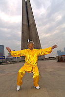 Chinese man practicing tai chi in the early morning in Huangpu Park (with the Monument to the People's Heroes in the background), Shanghai, China