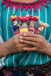 Child holding small handmade dolls in her hands, Chichicastenango, Guatemala