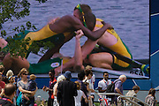 Seen on a giant screen in the Olympic Park, South Africa's gold medallist rowers Sizwe Ndlovu, John Smith, Matthew Brittain and James Thompson celebrate after winning the men's lightweight four rowing finals during the London 2012 Olympics. Spectators pass by as the team members celebrate with emotional hugs in their winning boat a few miles away in west London. This land was transformed to become a 2.5 Sq Km sporting complex, once industrial businesses and now the venue of eight venues including the main arena, Aquatics Centre and Velodrome plus the athletes' Olympic Village. After the Olympics, the park is to be known as Queen Elizabeth Olympic Park.