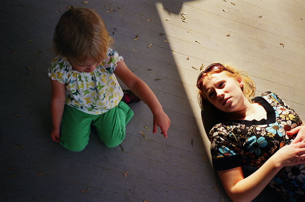 Melissa Eich, 22, lays in the afternoon light on the porch while her daughter Madelyn, 2, sits whining next to her on Saturday, April 17, 2010.