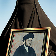 A woman holds a framed picture of Moqtada al-Sadr at a demonstration in Baghdad, Iraq on the 4th Jan 2004.