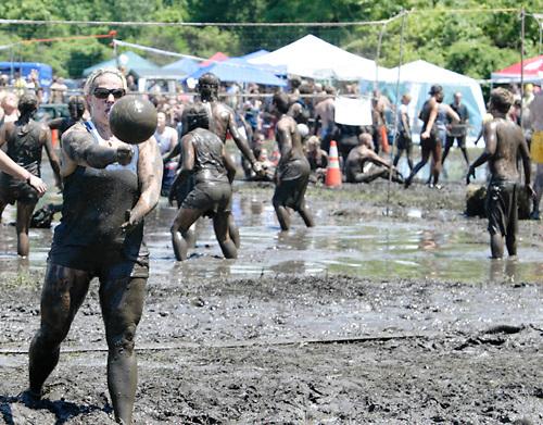Carla Ruble of Washington Township serves a mud coated ball during MuddyGras, the 20th annual mud volleyball for Epilepsy at Wegerzyn Gardens MetroPark in Dayton, Saturday, July 10, 2010.