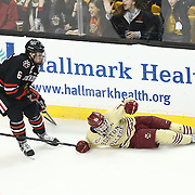 Mike Gunn #6 of the Northeastern Huskies skates past a fallen Johnny Gaudreau #13 of the Boston College Eagles during The Beanpot Championship Game at TD Garden on February 10, 2014 in Boston, Massachusetts. (Photo by Elan Kawesch)
