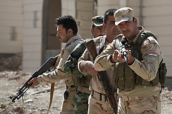 © Licensed to London News Pictures. 09/03/2015. Erbil, Iraq. Kurdish peshmerga fighters line up as they learn how to enter a garden during an urban warfare training session run by German soldiers at a partially finished housing estate near Erbil, Iraq. <br /> <br /> The training is part of a four week platoon level infantry training package run by coalition forces aimed at improving the efficiency of the Iraqi Security Forces. Photo credit: Matt Cetti-Roberts/LNP