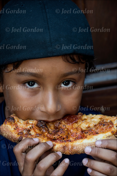 Portrait of Luca eating pizza outdoors on front steps on summer day