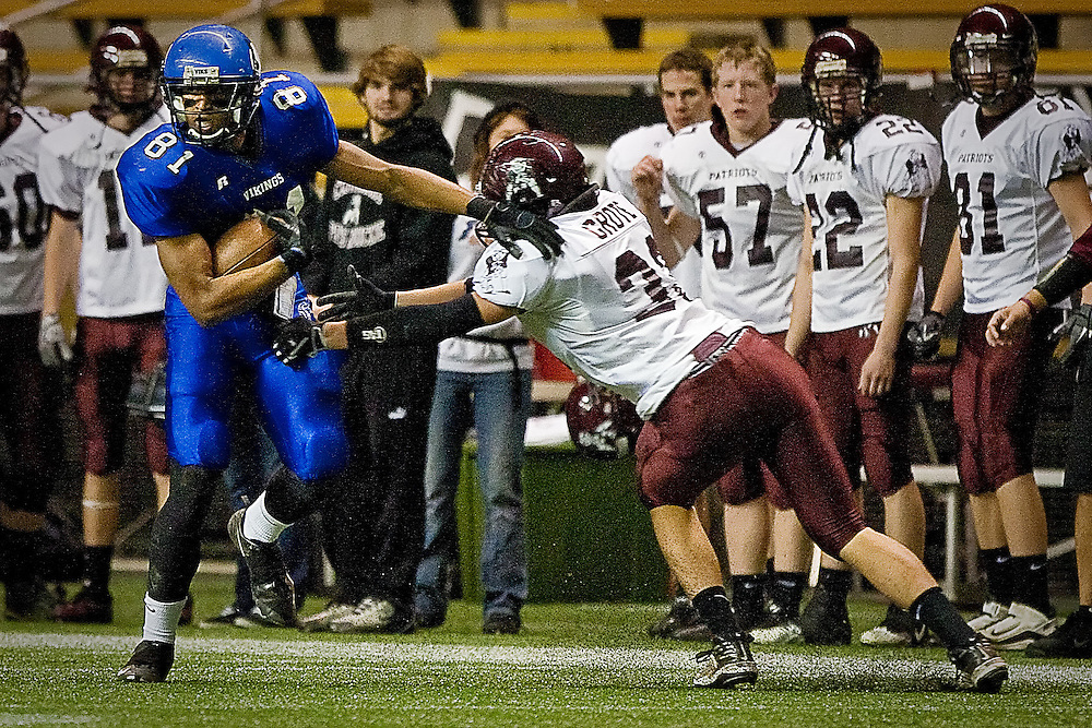 Coeur d'Alene High receiver Deon Watson brushes aside defender Brett Grote from Centennial as he goes up the sideline for his first of two touchdowns during the 5A State Championship game Friday at the University of Idaho Kibbie Dome.