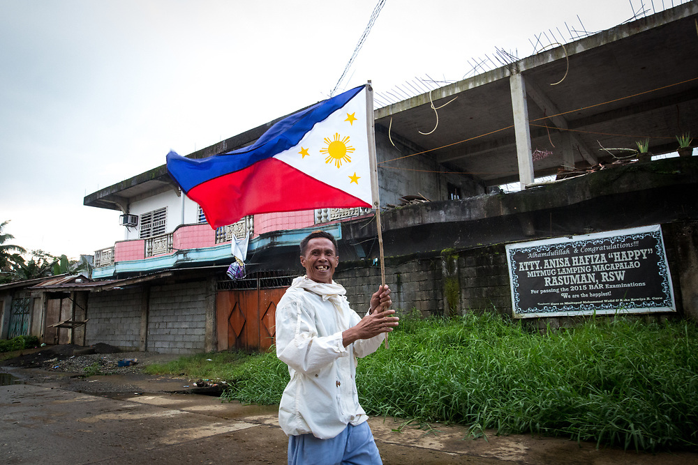 MARAWI, PHILIPPINES - JUNE 11: Civilian runs with a Philippine flag in war-torn Marawi City in preparation for the celebration of Independence Day on June 12, Lanao del Sur, Philippines, June 11, 2017. As fighting rages on for the third week, the display of flags is a show of force in an attempt to boost troop morale. (Photo: Richard Atrero de Guzman/NUR Photo)