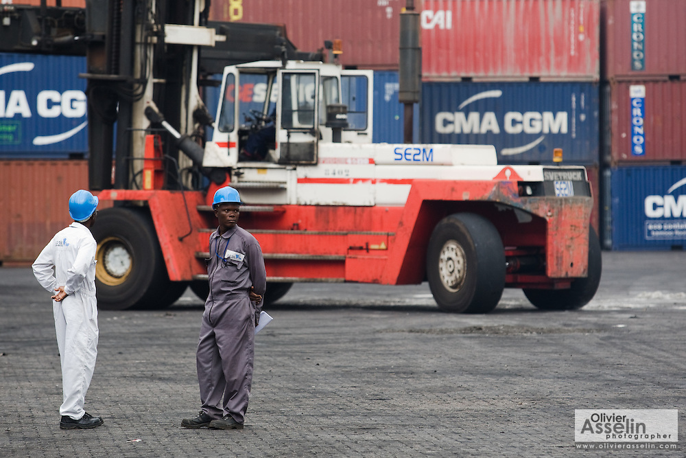 Workers stand by as a tractor carries containers at the sea port in Lome, Togo on Friday October 3, 2008.