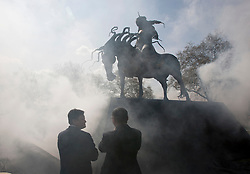 © licensed to London News Pictures. London, UK 14/04/2012. Security Guards watch as a sculpture of Genghis Khan by Dashi Namakov is unveiled at  Marble Arch in central London on April 14, 2012. Photo credit: Tolga Akmen/LNP