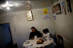 A man eats breakfast with his daughter, who has lead poisoning, in La Oroya, Pery.
