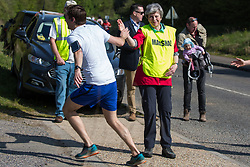 Maidenhead, UK. 19th April, 2019. Prime Minister Theresa May gives a runner a high five as she serves as a marshal at the annual Maidenhead Easter 10 charity race on Good Friday.