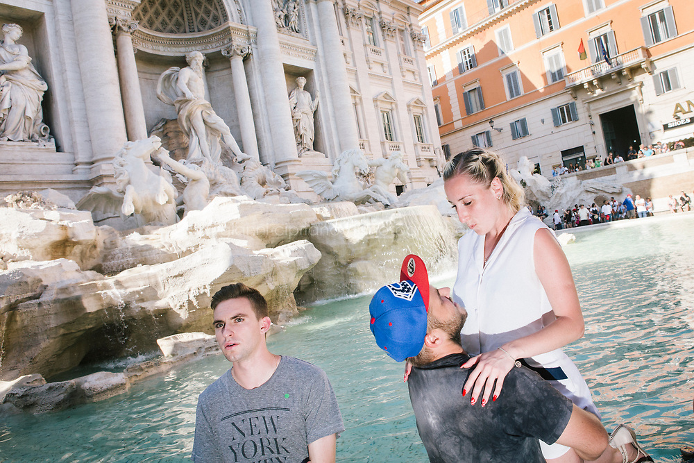 ROME, ITALY - 20 JUNE 2017: Tourists pose for pictures by the Trevi Fountain in Rome, Italy, on June 20th 2017.<br /> <br /> The warm weather has brought a menacing whiff of tourists behaving badly in Rome. On April 12, a man went skinny-dipping in the Trevi fountain resulting in a viral web video and a 500 euro fine.<br /> <br /> Virginia Raggi, the mayor of Rome and a national figurehead of the anti-establishment Five Star Movement,  issued an ordinance involving harsher fines for eating, drinking or sitting on the fountains, for washing animals or clothes in the fountain water or for throwing anything other than coins into the water of the Trevi Fountain, Bernini&rsquo;s Four Fountains and 35 other city fountains of artistic or historic significance around the city.  &ldquo;It is unacceptable that someone use them to go swimming or clean themselves, it&rsquo;s an historic patrimony that we must safeguard,&rdquo; Ms. Raggi said.