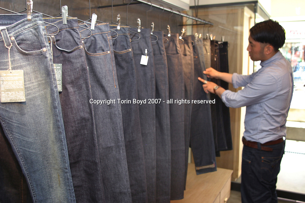 "This is Eliminator, a men's clothing store located in the fashionable Daikanyama district of Tokyo. In business for seven years, this hipster boutique sells ""restricted wear items"" based on UK street fashion. In explaining the concept of this shop, press manager Masahide Takahashi points out ""we offer a mix of blue jeans and high level designer wear, that is our philosophy"". He adds ""denim is our most important element"". Some of the designer labels Eliminator sells are; By Raf Simons (Belgium), Kim Jones (UK), SUPERFINE (UK), Colur (USA) and Brand of Outsiders (USA). They also offer the retro Levi's Red label, as well as blue jeans from Europe and Japan. This is their only shop in Japan. Addl note: the man in this is photo is a staff member of Eliminator and is seen here working. However, there was a restriction on showing his full face and giving his identity details. The pants he is wearing are Levi's Red, a retro re-issue of old Levi's jeans and his shirt is by Brand of Outsiders, designed by Scott Sternberg."