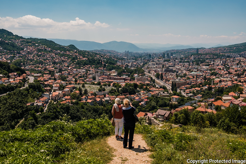 Two women take photos of the city of Sarajevo of an elected vantage point. For over 4 years shells and sniper fire rained down from these very hills onto the citizens of Sarajevo from 1992 until 1996.