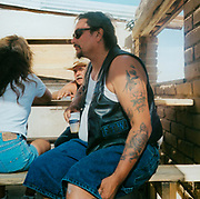 Man sitting on a bench wearing a leather waistcoat USA 1990's