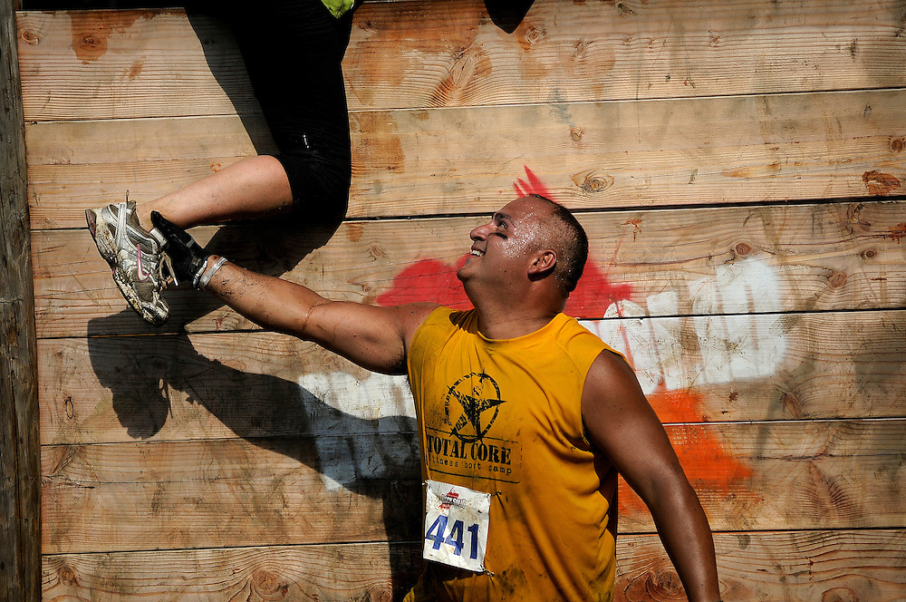 A participant assists another over a wall during the Rock Solid Mud Run held at Old Bridge Township Raceway Park in Englishtown on August 6. Rock Solid Mud Run is an all-terrain adventure that involves mastering obstacles along either a five or ten-mile course. Participants ran, swam, crawled, climbed, jumped while covering four motocross tracks, hundreds of acres of woods, three lakes, and two asphalt racetracks.