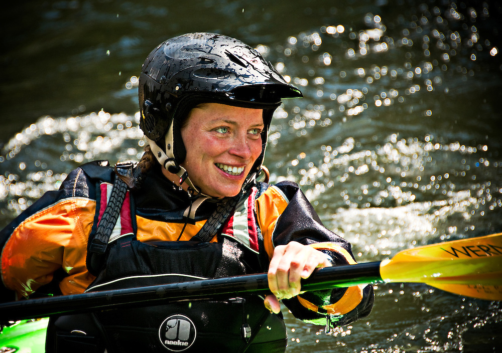 Idaho. Middle Fork Salmon River. Female kayaker smiling while on whitewater. MR