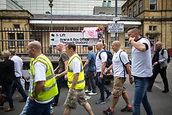 © Licensed to London News Pictures . FILE PICTURE DATED 26/06/2017 of fire fighters and staff from Manchester Central Fire Station , wearing symbolic Manchester bee t-shirts , passing Manchester Arena during a walk from Manchester Central Fire Station to St Ann's Square in Manchester City Centre for a short ceremony and release of 22 doves , in commemoration of the 22 people killed in a murderous terrorist attack , carried out by Salman Abedi , following an Arina Grande concert at the Manchester Arena , on 22nd May 2017 . Local fire crews have expressed frustration , laid bare in the Kerslake Review published today (27th March 2018) after they were held back from attending to support other emergency services for nearly two hours after the bombing , on the night of the attack . Photo credit : Joel Goodman/LNP