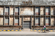 A man on his bicycle rides along an old factory facade in Mawlamyine, Myanmar, Southeast Asia