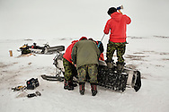 Rangers try to fix a broken suspension from a snowmobile in Baring Bay on Devon Island. Driving on solid and bumpy icepack instead of usual powder snow while towing a quarter ton komatik sled cause frequent mechanical failures. Snowmobile are ferried back by helicopter or ski equipped aircraft that resupply with a spare vehicle.  21 April 2012. Rangers are army units that mix local volunteers, here Inuits, and professional military acting as eyes and ears in the most remote areas of northern Canada.
