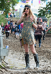 © Licensed to London News Pictures. 13/06/2015. Isle of Wight, UK.  A festival goer brushes her teeth in the  muddy conditions at Isle of Wight Festival 2015 on the morning of Saturday Day 3.  Yesterday suffered torrential rain all afternoon and evening, after a first day of warm sun.  This years festival include headline artists the Prodigy, Blur and Fleetwood Mac.  Photo credit : Richard Isaac/LNP