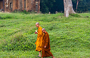 Two Buddhist monks walking and talking at Angkor Thom Temple, Angkor Wat Archeological Park, Siem Reap, Cambodia.
