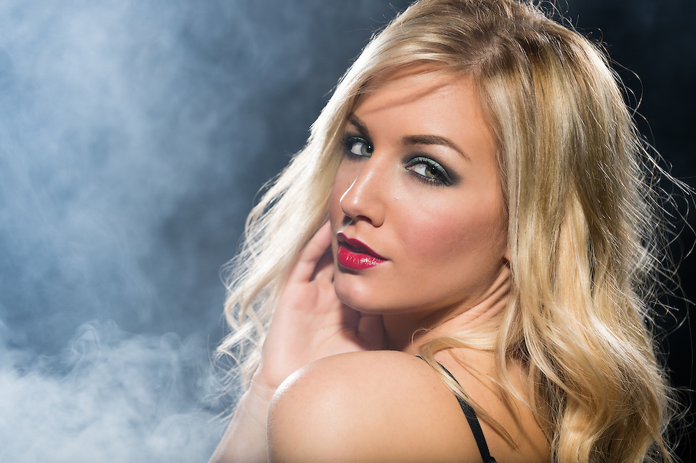 Portrait of sensual blonde woman looking at camera over her shoulder.