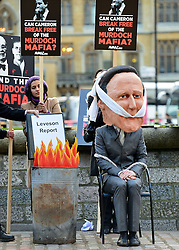 © Licensed to London News Pictures. 29/11/2012. CITY/TOWN e.g Windsor, UK Campaigners dressed as Lord Levenson and David Cameron tear sheets from a mock Leveson report outside the Leveson Inquiry today 29th November 2012. Photo credit : Stephen Simpson/LNP