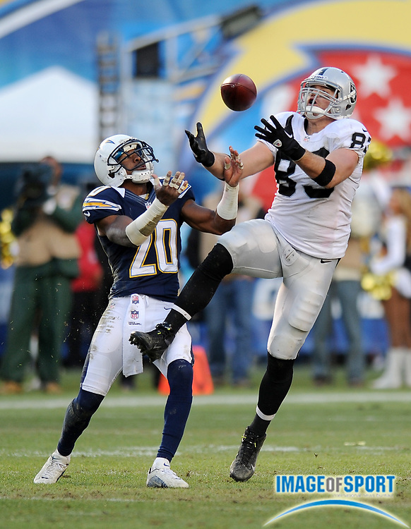 Dec 30, 2012; San Diego, CA, USA;  Oakland Raiders tight end Brandon Myers (83) bobbles the ball as San Diego Chargers cornerback Antoine Cason (20) defends on the play at Qualcomm Stadium.