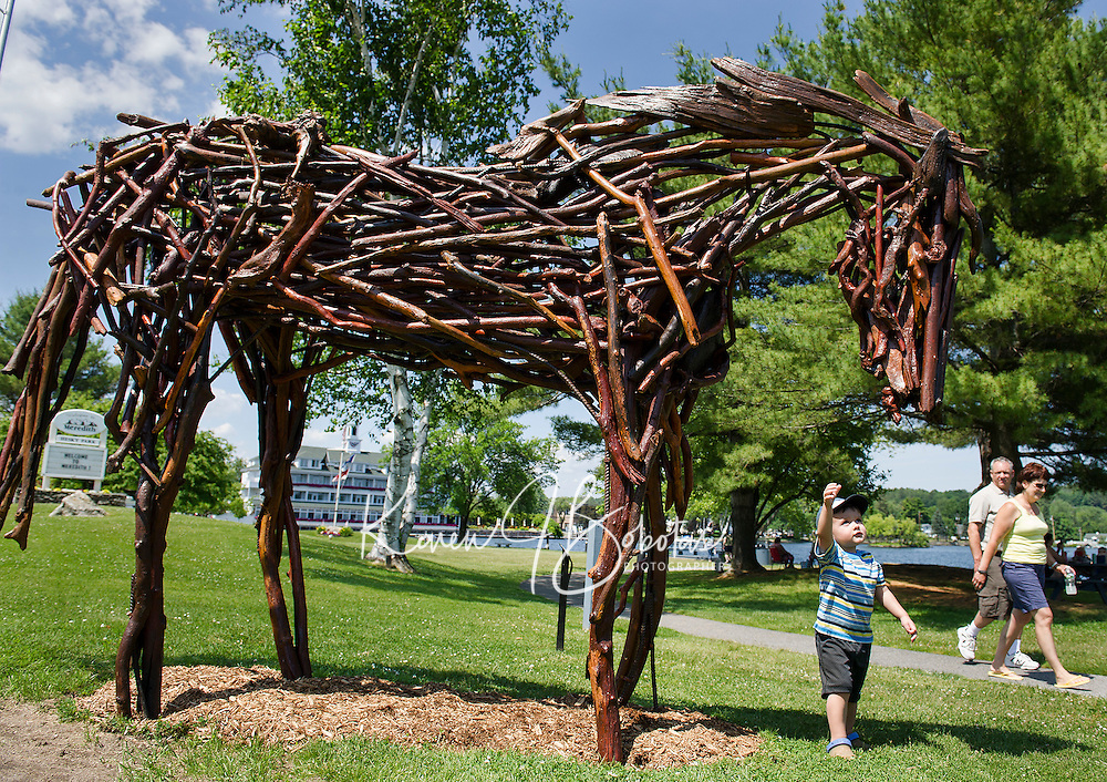 "Keegan Rodday of Hanover, MA reaches up to pet ""Horse"" made by Rita Dee of Bennington, VT as part of Meredith's Sculpture Walk.  (Karen Bobotas/for the Laconia Daily Sun)"