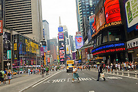 Times Square features electric neon billboards, traffic, taxis, pedicabs, and plenty of people walking.