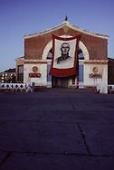 Mongolia. Khovd. Sukhe Bator painting in front of the theater     / affiche de suke bator devant le theatre  Khovd  Mongolie 5. Bannière à l'effigie de SUKBAATAR. . Seul monument imposant de la place centrale de la ville de QOVD, le théâtre se présente comme un lieu propice pour commémorer le 80ème anniversaire du combat dirigé par MAGSARJAV et DAMDINSUREN en 1912, contre la garnison mandchoue qui occupait les lieux. Les révolutionnaires mongols ont vu là le symbole des luttes pour l'autonomie et l'indépendance de leur pays qui seront menées à la même époque par SUKBAATAR. (Ville de QOVD, à l'ouest de la Mongolie, le 13 juillet 1992).