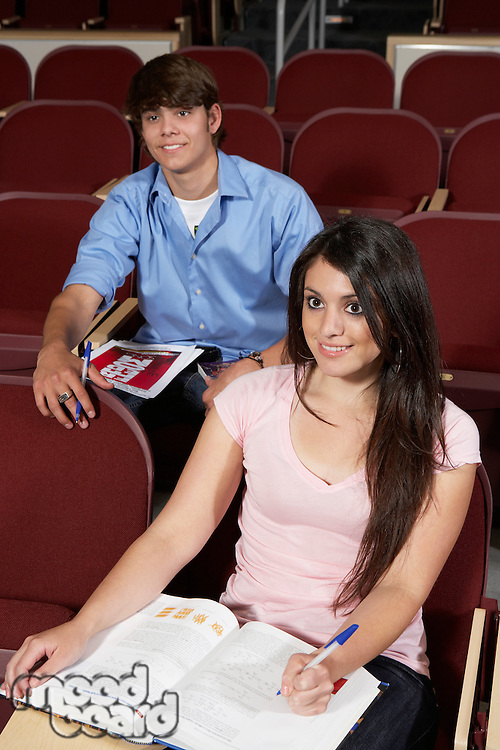 Two college students in classroom, smiling