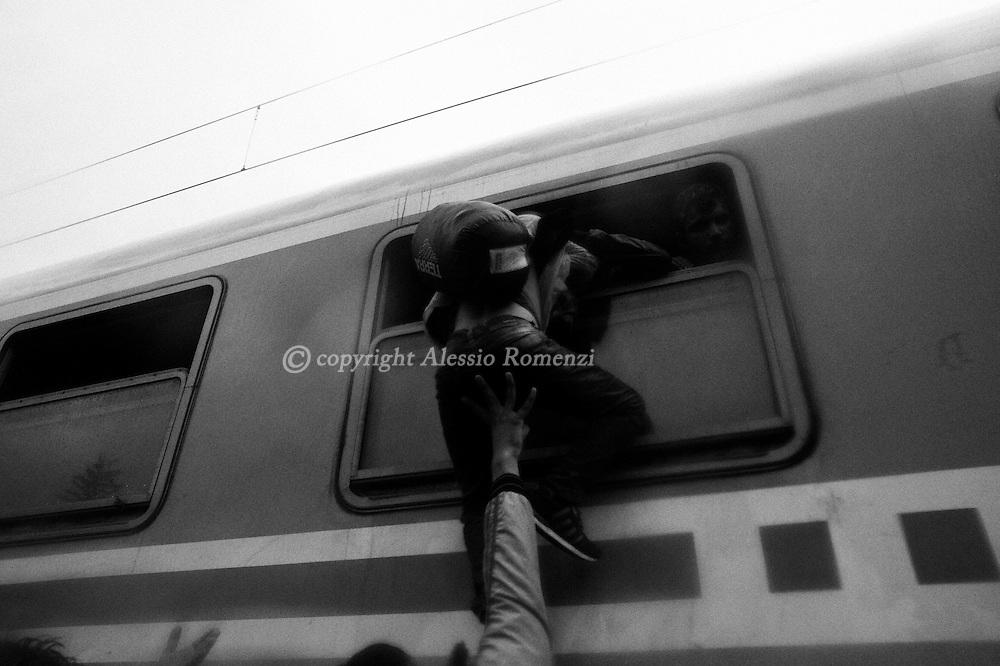 Croatia: Migrants board through a window a train heading to Zagreb Tovarnik railway station, near the official border crossing between Croatia and Serbia. Alessio Romenzi