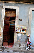 A girl walks past a photo studio in Havana, Cuba.