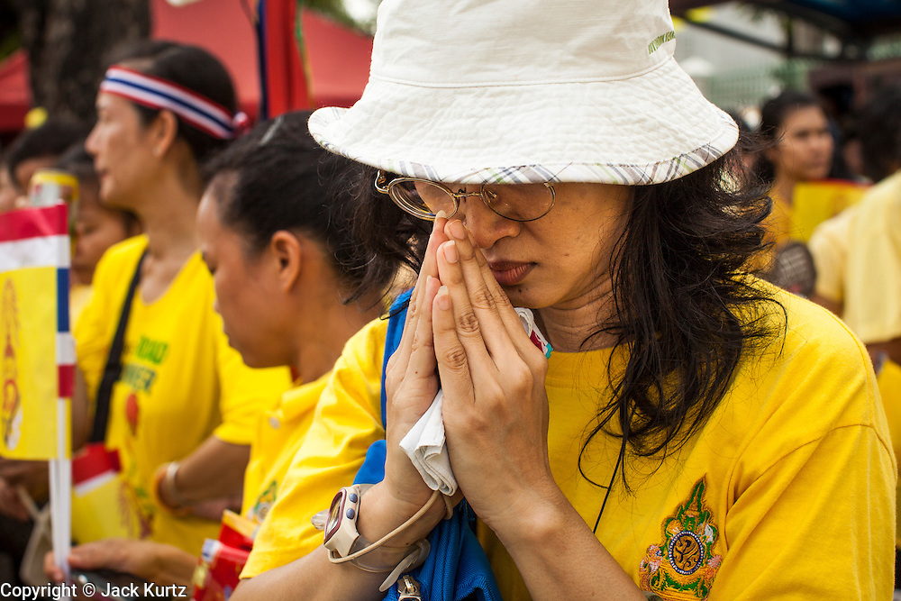 05 DECEMBER 2012 - BANGKOK, THAILAND:  A woman on the Royal Plaza Wednesday prays while Bhumibol Adulyadej, the King of Thailand, speaks during his public audience at the Mukkhadej balcony of the Ananta Samakhom Throne Hall. December 5 is a national holiday. It's also celebrated as Father's Day. Celebrations are being held across the country to mark the birthday of Bhumibol Adulyadej, the King of Thailand.   PHOTO BY JACK KURTZ