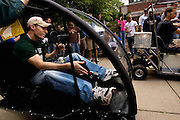 Adam Koloff, 20, a mechanical engineering student starts up one of the electric cars before his test drive in front of Stocker Center on Saturday, May 6th.