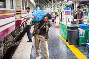 17 APRIL 2013 - BANGKOK, THAILAND:  A man in Hua Lamphong Train Station in Bangkok carries his belongings to a waiting train to go back to his province after Songkran. Songkran, the traditional Thai New Year, is the busiest time of the year for Thai domestic travel. Many people in Bangkok return to their home provinces for the holiday and some people in the provinces travel to Bangkok for the holiday. Songkran, usually a three day holiday, was five days this year because the official days on the weekend. Trains and buses coming into Bangkok were reported to be fully booked and the State Railway of Thailand added extra trains and carriages to accommodate the crowds.   PHOTO BY JACK KURTZ