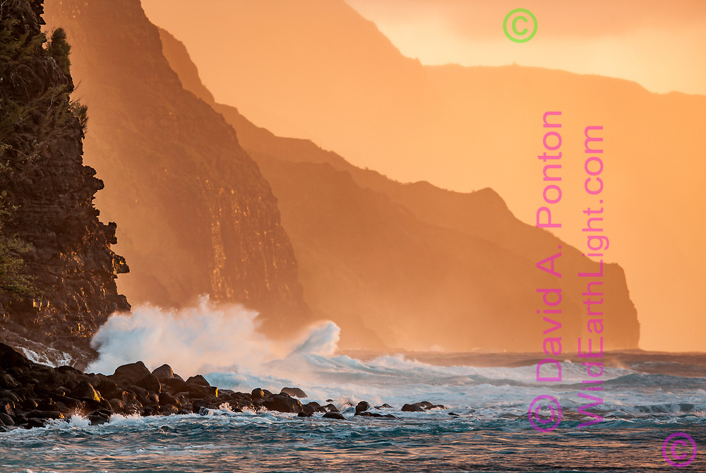 Ocean waves crash against cliffs on the rugged Na Pali Coast  in the light of the setting sun. Kauai, Hawaii, © 2010 David A. Ponton