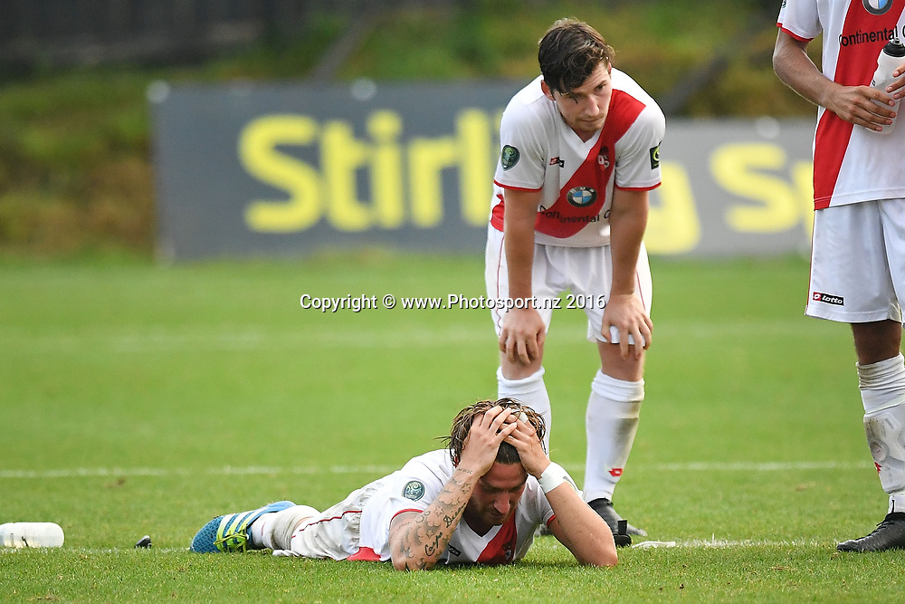 Waitakere's Pascal Reinhardt (Bottom) with team mate Stefen Thelen sit dejected after their loss during the Premiership semi-final football match between Wellington & Waitakere at David Farrington Park in Miramar on Sunday the 26th March 2017. Copyright Photo by Marty Melville / www.Photosport.nz