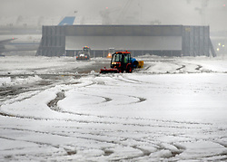 © Licensed to London News Pictures. 05/02/2012, London, UK. A snow plough clears snow from Heathrow Airport. Planes in the snow at Heathrow Airport today 05/02/12. The airport has cancelled a third of its flights because of the snow. Heavy snow has fallen over many parts of the UK overnight. Photo credit : Stephen Simpson/LNP