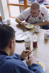 Two young men eating lunch in café area of day centre for homeless and vulnerably housed young people,