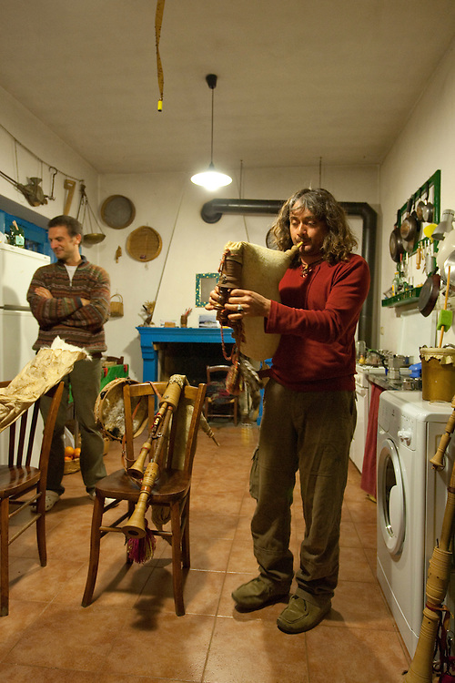 Quirino Valvano plays the Zampogna, a traditional Italian instrument, in the kitchen of the Agriturismo Asklepios; Giuseppe Cosenza (owner of the Agriturismo) is listening; Basilicata/Calabria, Pollino National Park, Italy. November 2008. Mission: Pollino National Park