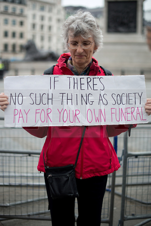 © Licensed to London News Pictures. 17/04/2013. London, UK. A protester holds placard during the funeral of former British Prime Minister Baroness Thatcher at Trafalgar square on April 17, 2013 in London, England. Photo credit : Peter Kollanyi/LNP